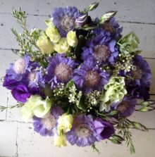 Blue and white bouquet of flowers which are hand tied