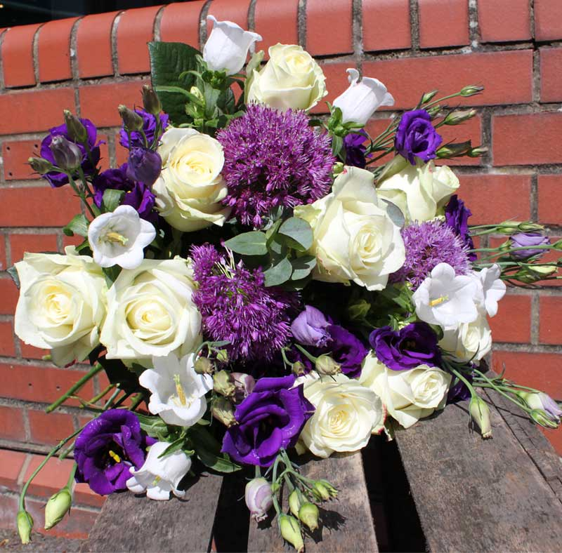 purple and white bouquet with displayed with brick background