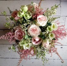 hand tied pink bouquet of flowers with wooden background