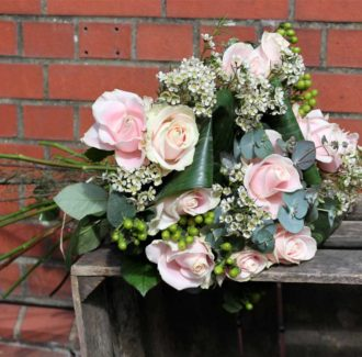 pink roses on wooden tray with brick background