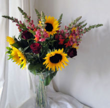 sunflowers and roses in vase with white background