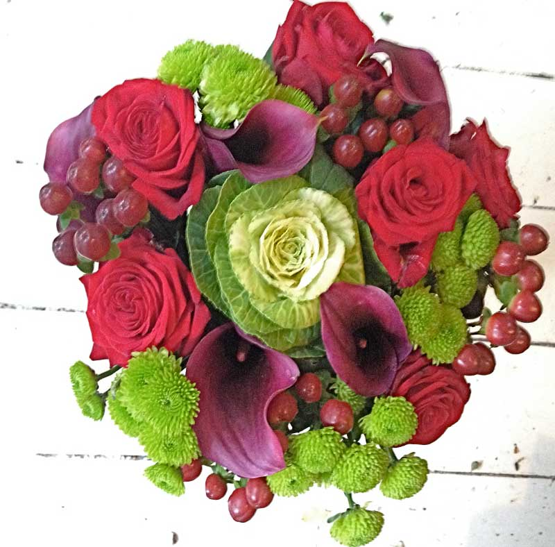 Red rose and lilly bouquet on white wood floor